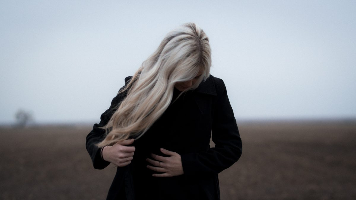 An image of a person with blonde hair standing in a field.