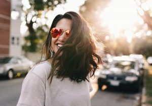 An image of a woman walking down the street with sunglasses on.